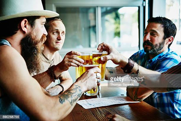 Group of friends toasting beers in restaurant