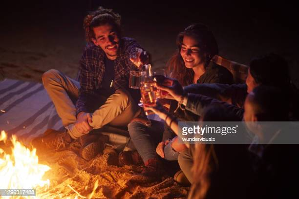 group of friends toasting drinks on beach bonfire at night - celebratory toast stock pictures, royalty-free photos & images