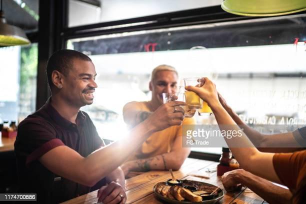 groep vrienden toasten in een bar/restaurant - friday stockfoto's en -beelden