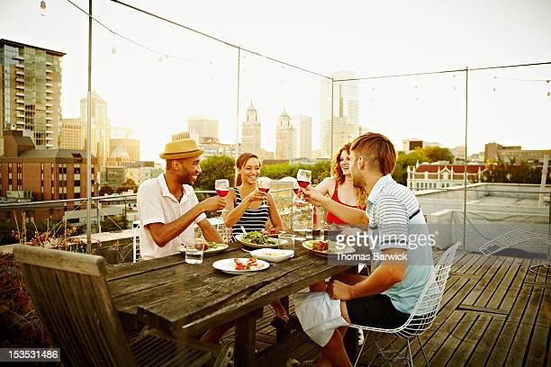 Group of friends toasting on rooftop deck