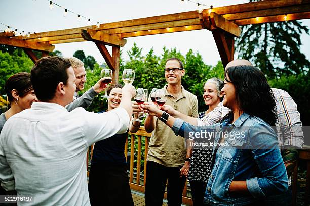 Group of friends toasting wine glasses on deck