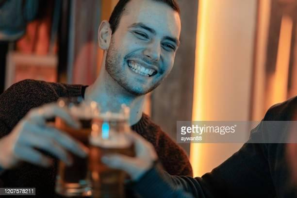 ビールで乾杯する友人のグループ - 肩越し ストックフォトと画像
