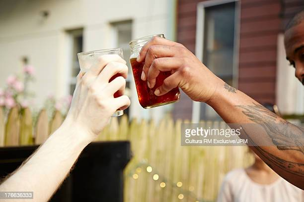 Group of friends toasting with drinks at garden party