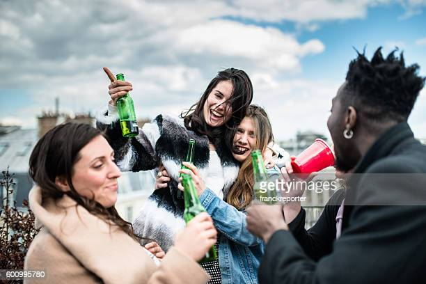 group of friends toasting with drinks  on the rooftop