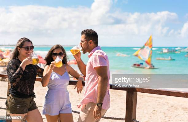 group of friends toasting with drinks on the tropical beach - porto galinhas stock photos and pictures