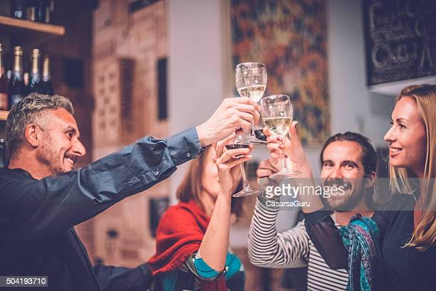 Group of Friends Toasting with Wine in a Wine Bar
