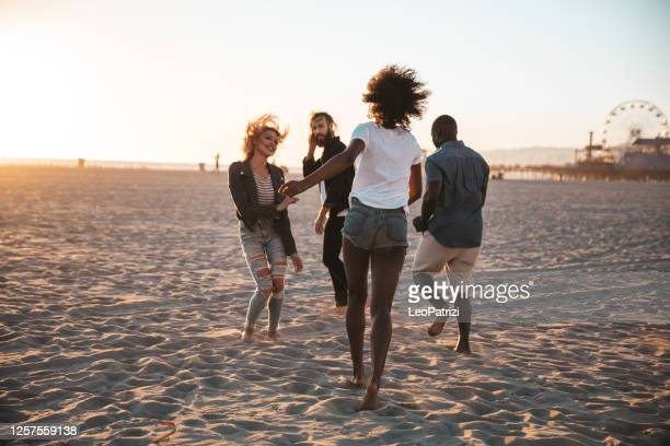 group of friends together in santa monica beach - santa monica stock pictures, royalty-free photos & images