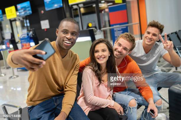 Group of friends traveling together and taking a selfie at the airport