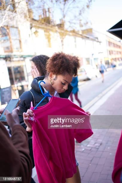 group of friends trying on vintage clothing outside a store - clothing stock pictures, royalty-free photos & images