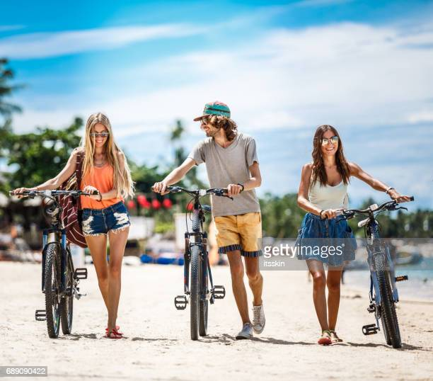 Group of friends - two girls and one guy - dragging their bicycle over a sandy beach