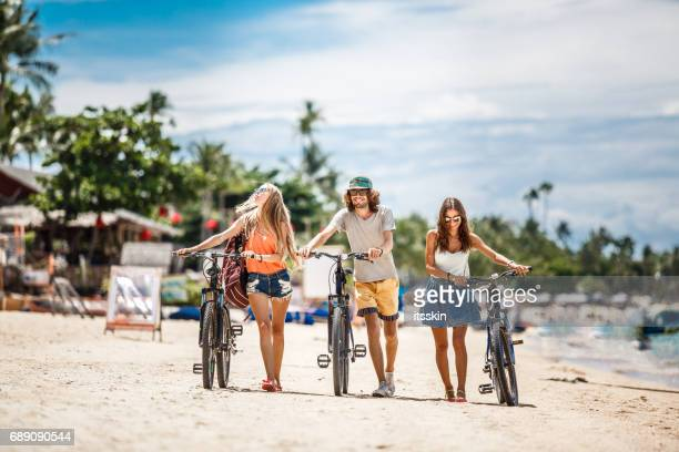 group of friends - two girls and one guy - dragging their bicycle over a sandy beach - ko samui stock photos and pictures