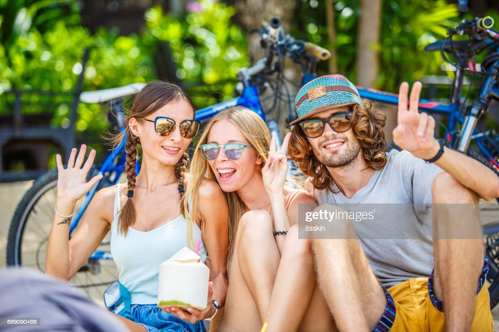 Group of friends - two girls and one guy - sitting on sand, having rest in the shade of trees. Little dog nearby. Bicycles behind them : Stock Photo