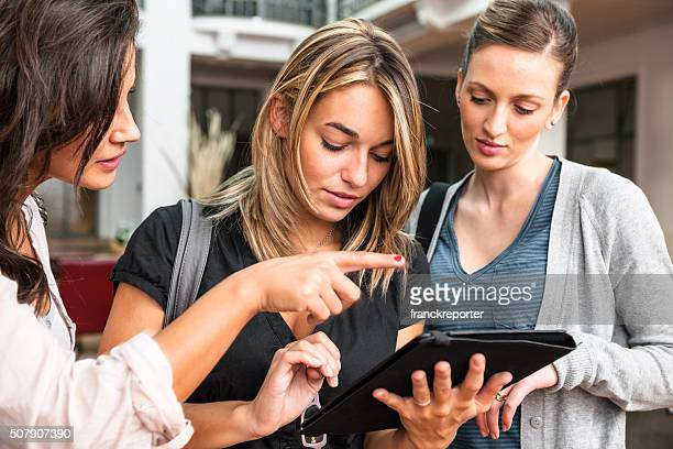 group of friends using a tablet at the university - college application stock photos and pictures