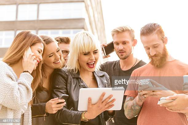 group of friends using digital tablet and smart phones outdoor - izusek stock pictures, royalty-free photos & images