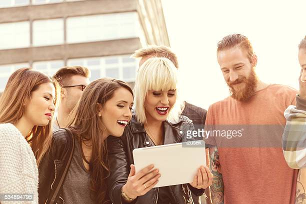 Group of friends using digital tablet outdoor