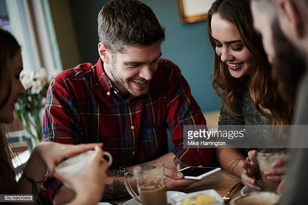 Group of friends using smart phone in cafe