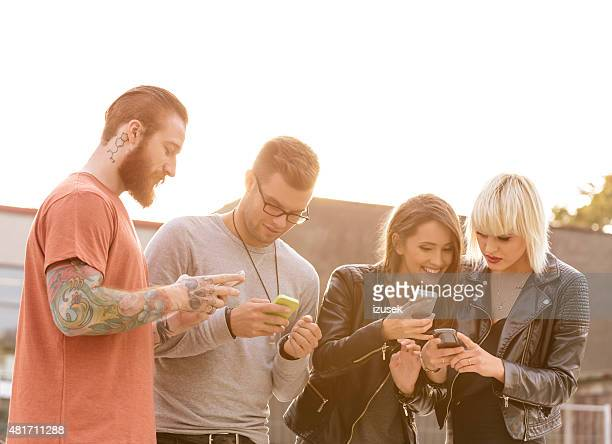 Group of friends using smart phones outdoor at sunset