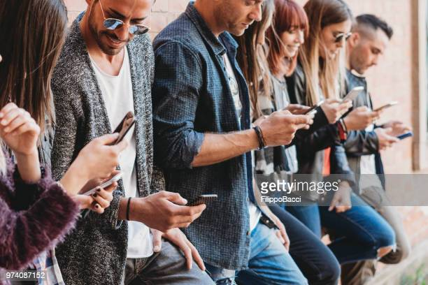 group of friends using smartphone outdoors - medium group of people stock pictures, royalty-free photos & images