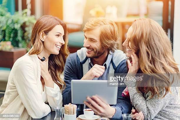 ご友人グループでタブレットを使用して、屋外カフェ