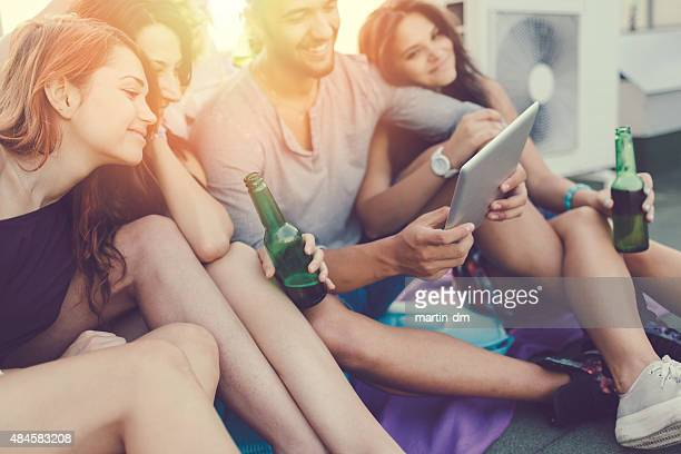 Group of friends using tablet pc on the rooftop