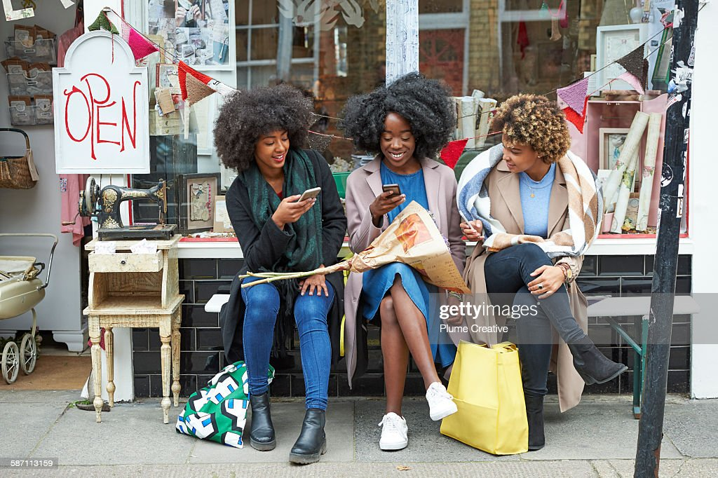 Group of friends using their mobile phones outside a shop. : Stock Photo