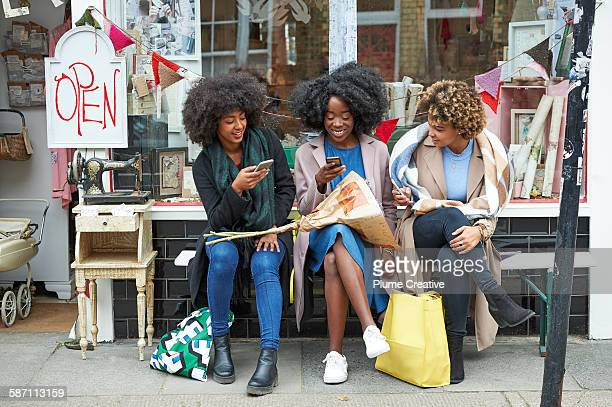 group of friends using their mobile phones outside a shop. - street market stock pictures, royalty-free photos & images