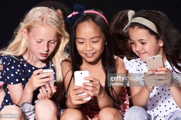 group of friends using their phones - child facebook stock photos and pictures