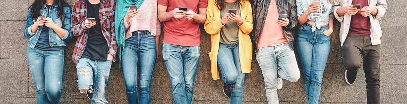 Group of friends using their smart mobile smartphones outdoor - Millennial young people addicted to new technology trends apps - Concept of people, tech, social media, generation z and youth lifestyle 1140773919