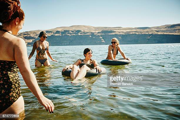 Group of friends wading and floating in river