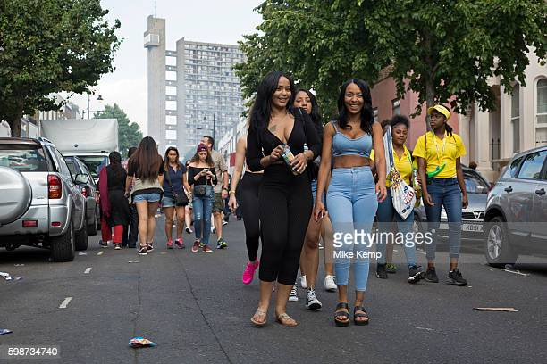 Group of friends walk along Golborne Road with Trellick Tower in the distance on Monday 28th August 2016 at the 50th Notting Hill Carnival in West...