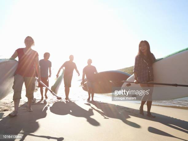 group of friends walking along beach with paddle boards in summer. - dougal waters stock pictures, royalty-free photos & images
