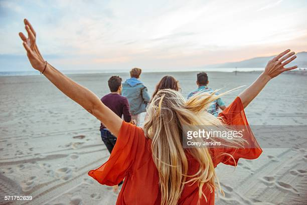 Group of friends walking along beach, young woman with arms in air, rear view