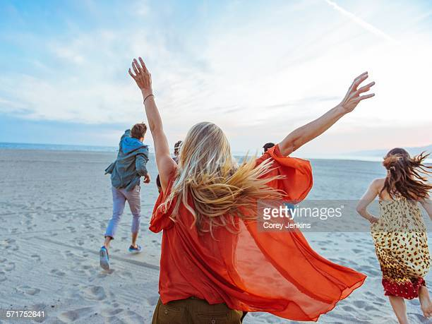 group of friends walking along beach, young woman with arms in air, rear view - サンタモニカ ストックフォトと画像