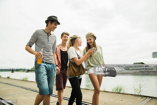 Group of friends walking at the riverside