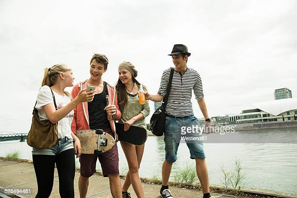 group of friends walking at the riverside - jugendliche stock-fotos und bilder