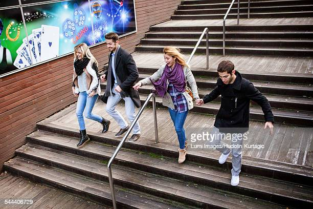 Group of friends walking down steps in town