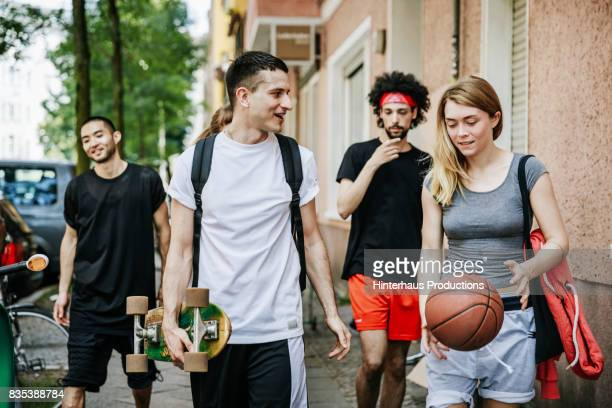 Group Of Friends Walking Home After Day Of Playing Basketball Together