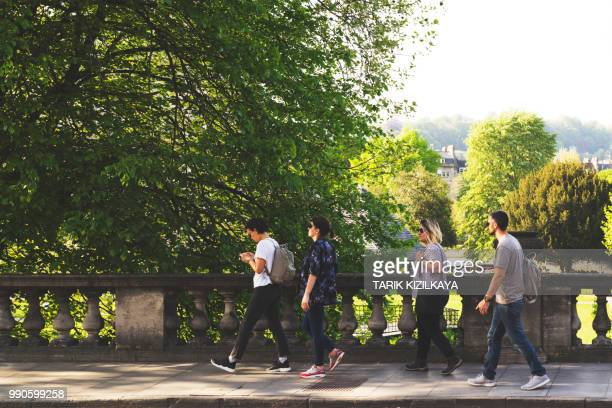 group of friends walking in bath city - somerset england stock photos and pictures