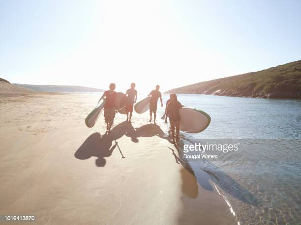 Group of friends walking on beach with SUP paddle boards.