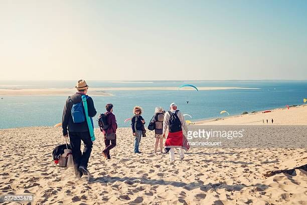 group of friends walking on beach with warm clothes. - aquitaine stock photos and pictures