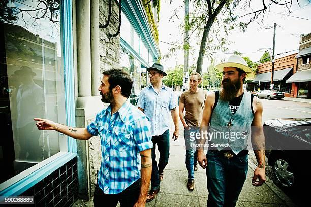 Group of friends walking on sidewalk past shops