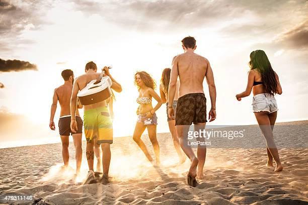Groupe d'amis marchant sur la plage au crépuscule