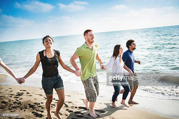 group of friends walking on the beach togetherness