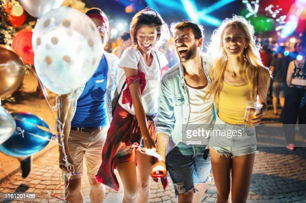 group of friends walking through a festival crowd. - festival goer stock pictures, royalty-free photos & images