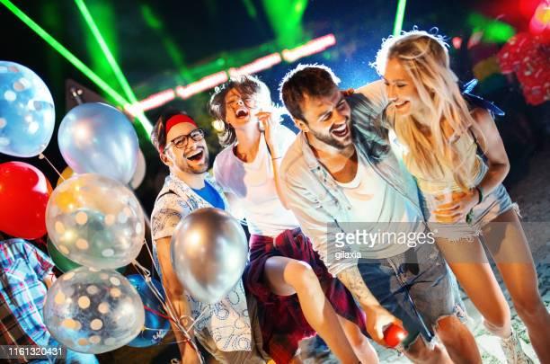 group of friends walking through a festival crowd. - gilaxia foto e immagini stock