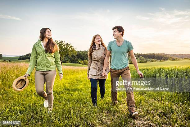 Group of friends walking through field