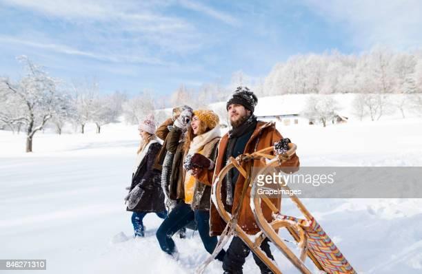 Gruppe von Freunden zu Fuß durch die Wiese im Winter.