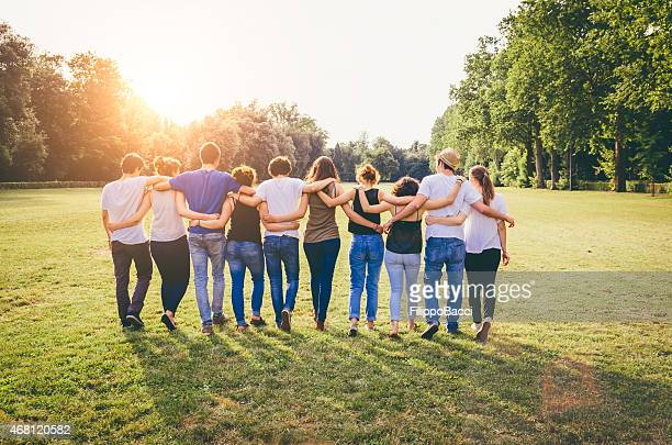 group of friends walking together - shoulder stock pictures, royalty-free photos & images