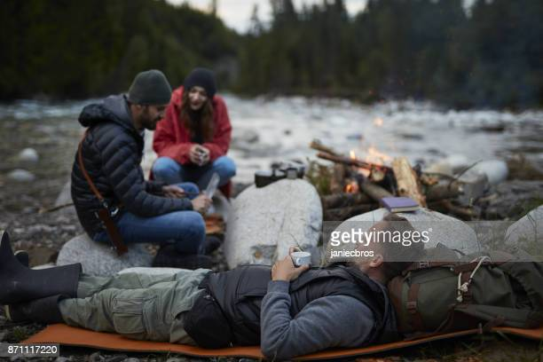 group of friends warming up by the fire - small group of people stock pictures, royalty-free photos & images