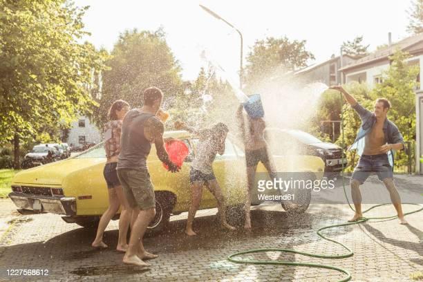 group of friends washing yellow vintage car in summer having fun - nur erwachsene stock-fotos und bilder